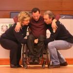 Esercitazione sulla disabilità: un disabile viene sollevato dalla sua carrozzina da due operatori della protezione civile durante una simulazione di soccorso