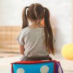 Covid-19 e autismo: nella foto una bambina di spalle seduta su un puf