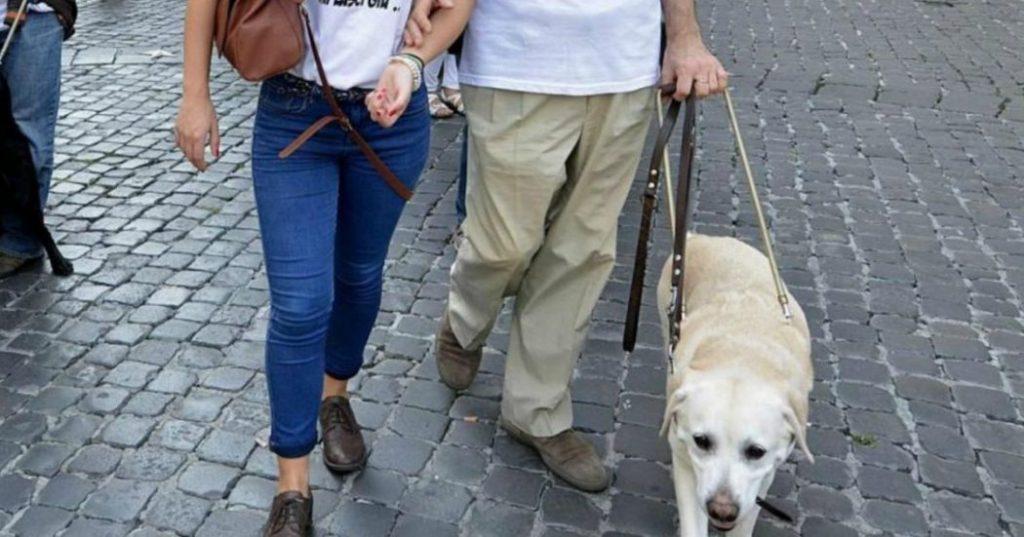 persona cieca con cane e accompagnatore per Coronavirus e disabilità visiva