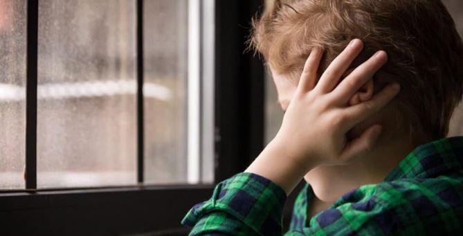 bambino con autismo di spalle alla finestra