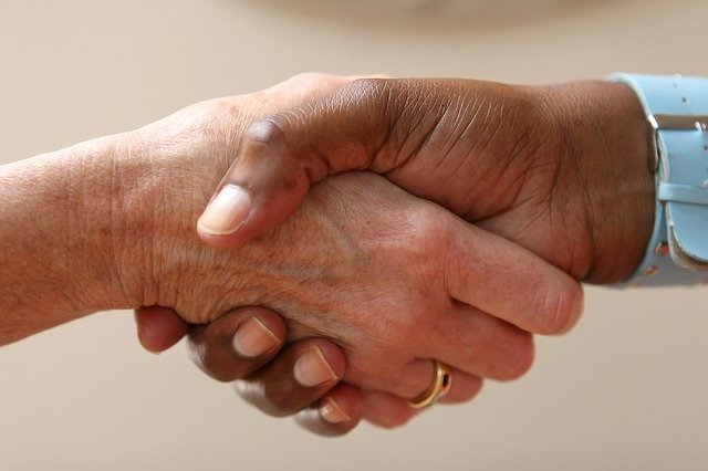 due mani che si stringono: AISM e Soccorso Senza Barriere si incontrano per siglare il protocollo d'intesa